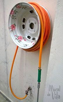 Upcycle an old tire rim (the wheel) into a hose reel. The wheel was painted and decorated with decoupage to serve as support for the garden hose.