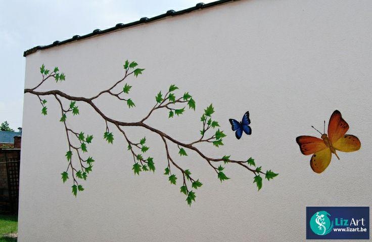 Muurschildering van een tak met vlinders op een tuinmuur