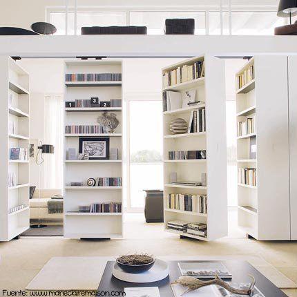 Una biblioteca que se abre y da paso al living.