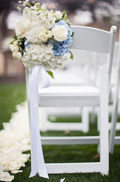 Fresh green grass is lined with white rose petals to create a natural aisle.