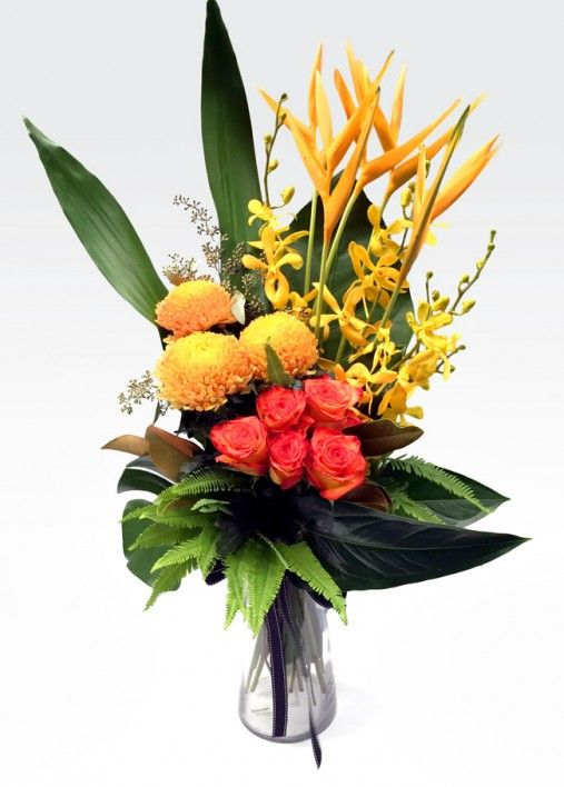 #Tutti_Fruitti -  Is a Vibrant vase arrangement of #tropical #flowers and seasonal blooms with lush tropical foliage. Arranged in a glass #vase for easy transport and maintenance.