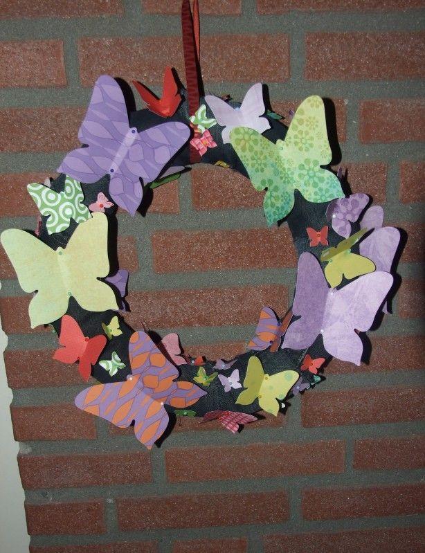 Krans:    gemaakt van strooien krans van Action daarover stukken van een oude spijkerbroek gewikkeld met allemaal verschillende maten en kleuren vlinders met knopspelden bevestigd.