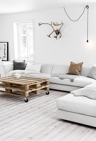 Nordic living room with white sofa, palette table, single pendant light bulb lamp