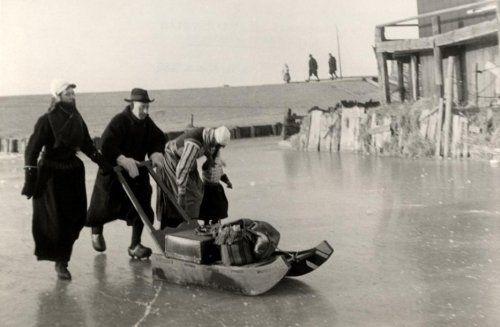 Tweede Wereldoorlog. Nederland. Tijdens de strenge winter van 1942 worden rond het eiland Marken de koffers op een slede vervoerd. De schaat...