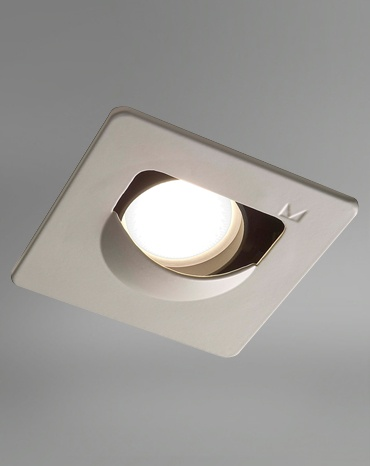 """Trend Assimétrico    Designer: Studio La Lampe +      Embutido fixo para """"wall washer"""".   Usar a 60 cm da parede.  Ideal para iluminação de quadros por oferecer uma luz homogênea e sem ogivas. Aro externo quadrado branco e alojamento para lâmpada em alumínio injetado, ambos pintados por processo eletrostático. Possui refletor interno assimétrico em alumínio, com acabamento anodizado natural e filtro fosco, inclusos. Instalação ao forro por mola em aço inox flexível e nicho circular de 92mm."""