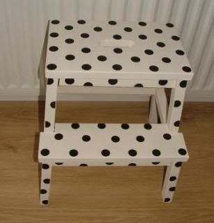 Ikea step stool, 2 coats of cream paint, punched out black circles from card stock. 2 coats of clear varnish.