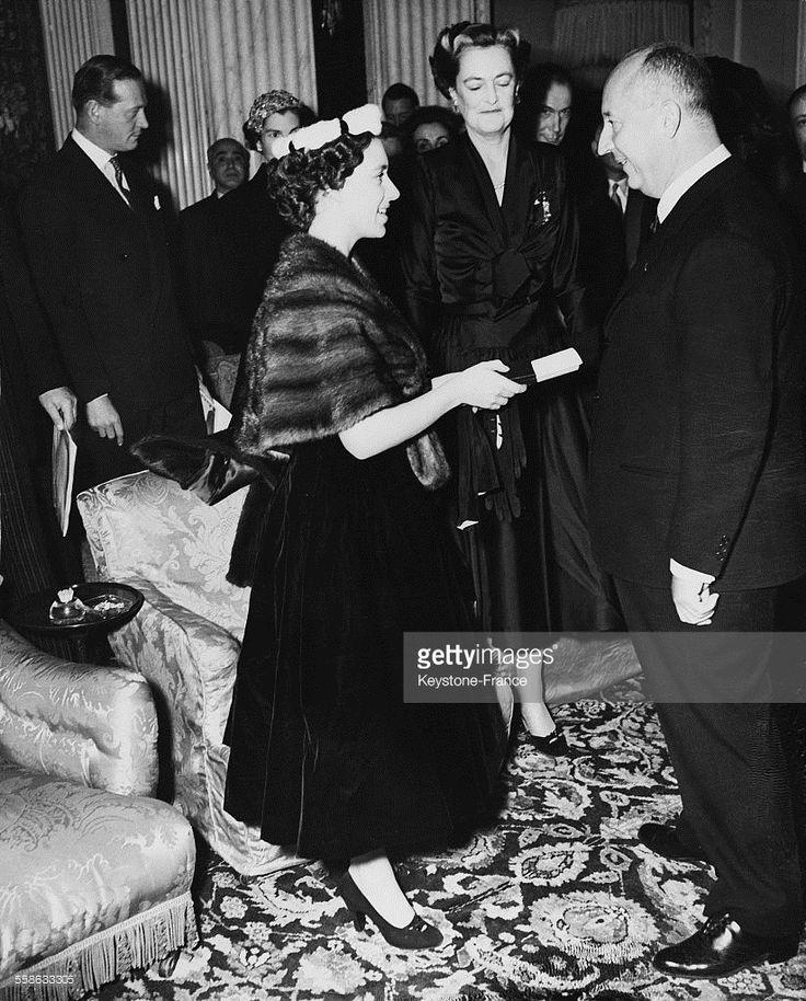 Le couturier Christian Dior recoit un certificat de membre de la Croix-Rouge des mains de la princesse Margaret d'Angleterre, a l'occasion d'une reception donnee au palais de Blenheim (residence de la duchesse de Marlborough, au second plan), le 3 novembre 1954 a Woodstock, Royaume-Uni. Le couturier vient alors de presenter sa derni?re collection Automne-hiver, et 1600 invit?s ont paye pour assister au defile.