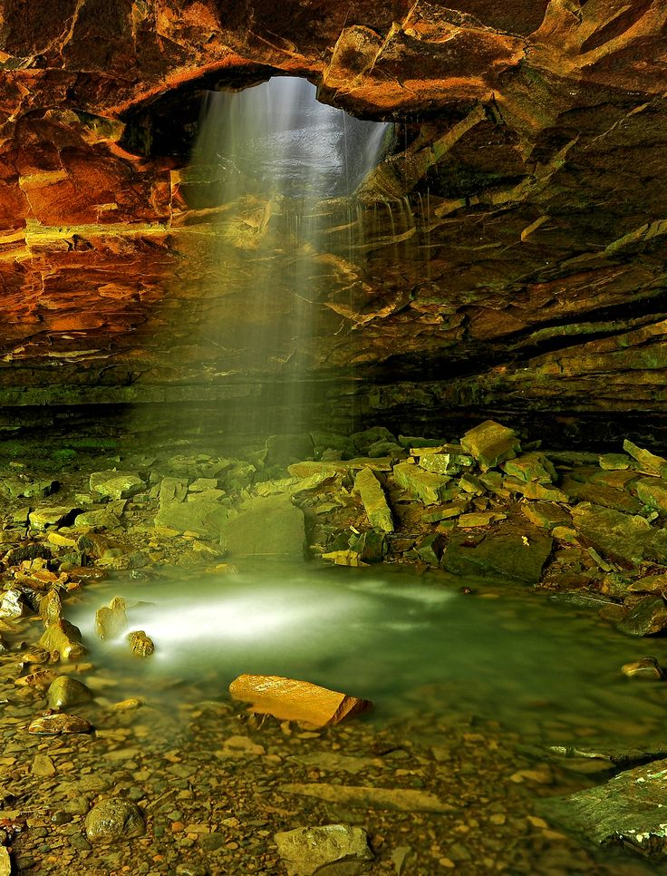 A waterfall shines through the top of a cave in Arkansas ...