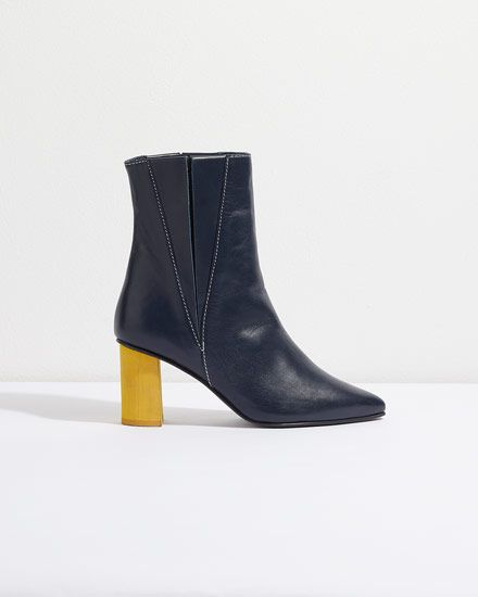 These pointed ankle boots feature a vibrant stained heel for maximum impact. Pair with jeans and sumptuous knits to channel the nautical vibes of soft navy leather, yellow wood and white stitching details.