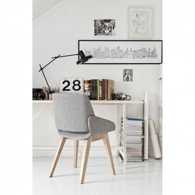 """""""Home Office com paleta de cores neutras e uma linda cadeira. O local possui decoração com quadros e livros, além de uma luminária na cor preta que…"""""""
