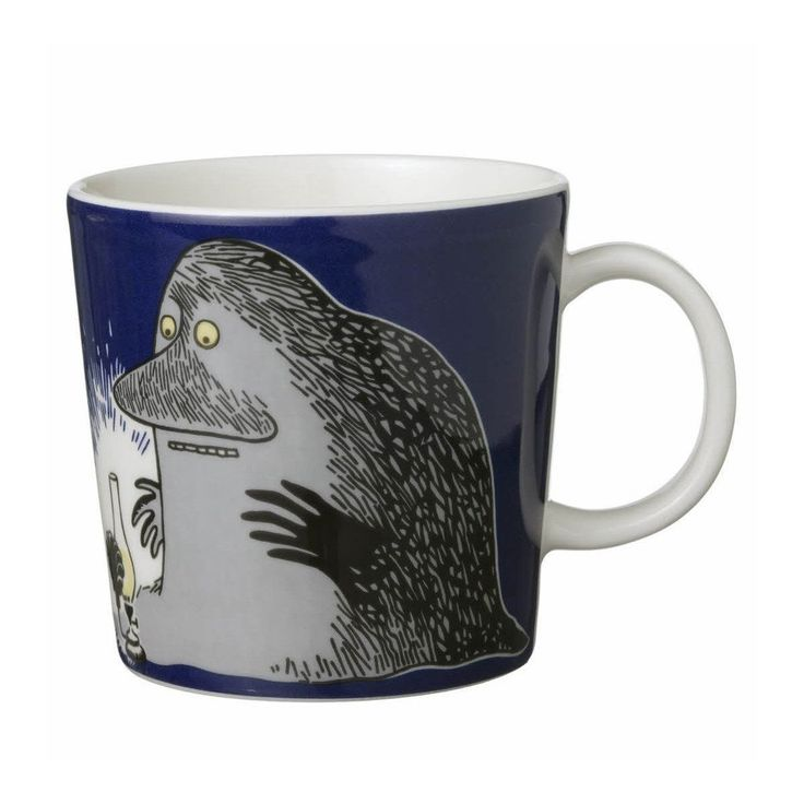 """This dark blue Moomin mug by Arabia from 2005 features the Groke looking at a night light. It's beautifully illustrated by Arabia artist Tove Slotte-Elevant and the illustration can be seen in the original book """"Moominland Midwinter"""" by Tove Jansson. Complete your collection of Moomin mugs with this wonderful piece. Also see the other parts of the ceramic Groke series by Arabia.ässä Arabian tummansinisessä mukissa vuodelta 2005 esiintyy Mörkö, joka katsoo yövaloa. Upean kuvituksen mukiin on…"""
