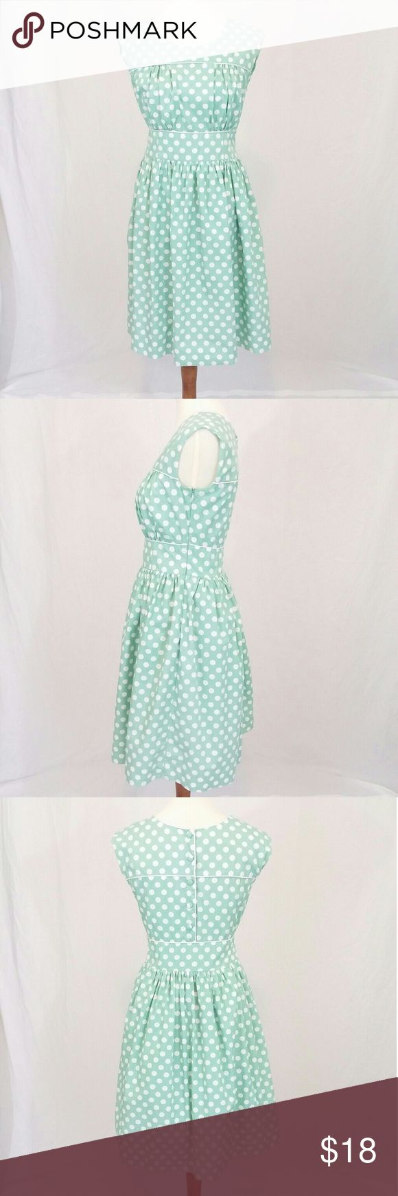 "Downeast Basics Vintage Style Polka Dot Dress Pretty as can be in mint green and polka dots! This cotton dress owes its 50's vibe to its piping along the neckline, bust, and waist as well as the button up detail in the back. Cinched in waist and gathered fabric in the bust will accentuate you in all the right ways. Measures approximately 35"" in the bust and 28"" in the waist. Length from shoulder to hem is 38"". Fully lined. Zip up on side. Please note this is a retro style dress, not actually…"