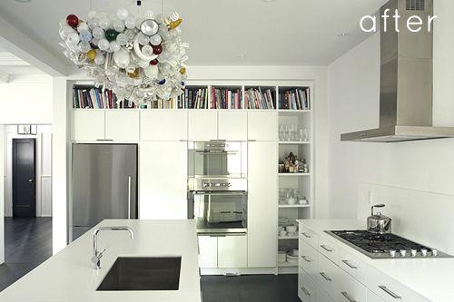 Ikea kitchen with custom shelving built around the units; dark oiled timber floors; black interior doors