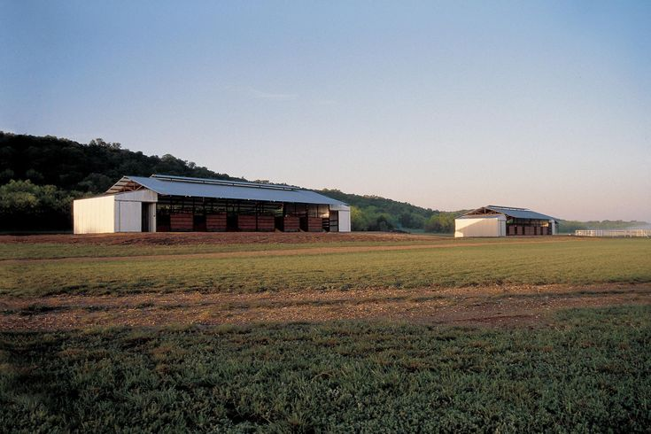 The design strength of these two open barn structures, with flanking saddlebag rooms, comes from the straightforward simplicity of form and materials. Designed as a habitat for the client's polo ponies, the use of welded reclaimed oil field pipe, rugged corrugated metal and soaring overhangs imparts an elegance that comes from using common materials to their maximum potential.Photography: Dawn Laurel