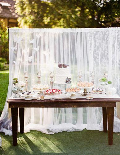 Una preciosa mesa de dulces con una cortina como fondo, via www.fiestafacil.com / A lovely sweet table with a gauze curtain as a backdrop, via www.fiestafacil.com