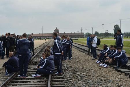 Quello che mi colpisce in questa foto è l'immagine della scolaresca. Questo scatto coincide con il punto di vista classico sul campo di Auschwitz, una costante iconografica. Sui binari sono seduti i ragazzi, come a cercare un attimo di riposo. Noto, come qualcosa di straniante, la tuta blu.