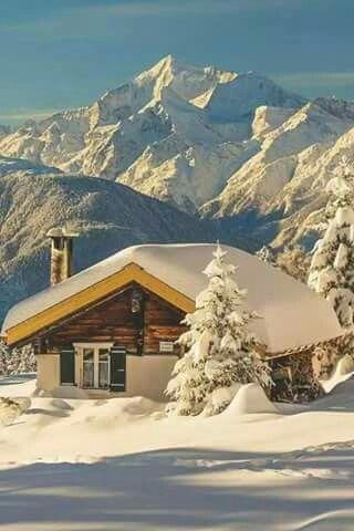 verschneite Hütte in einer verschneiten bergigen Landschaft