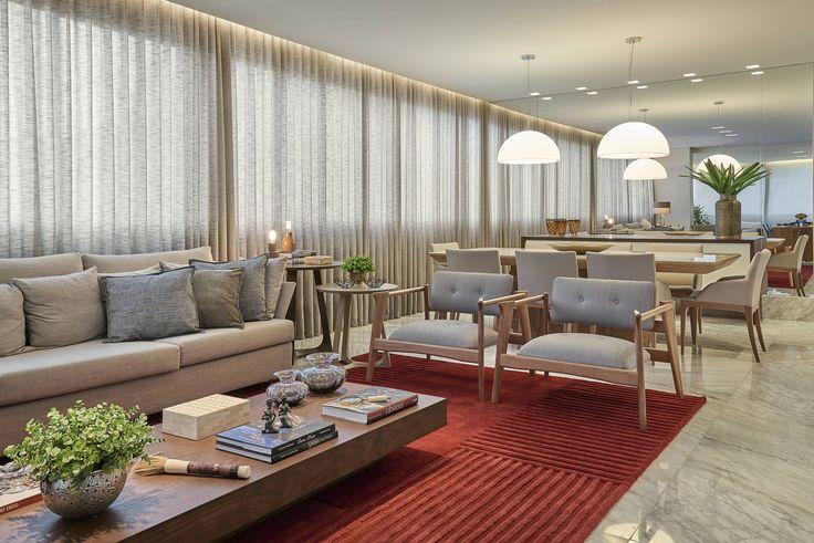 Sala Estar por Amis Arquitetura - Sala ampla com sofa em linho, poltronas em madeira e linho e tapete vermelho. Mesa de jantar em madeira com vidro pintado, cadeiras em linho. Pendentes iluminados e parede revestida em espelho.