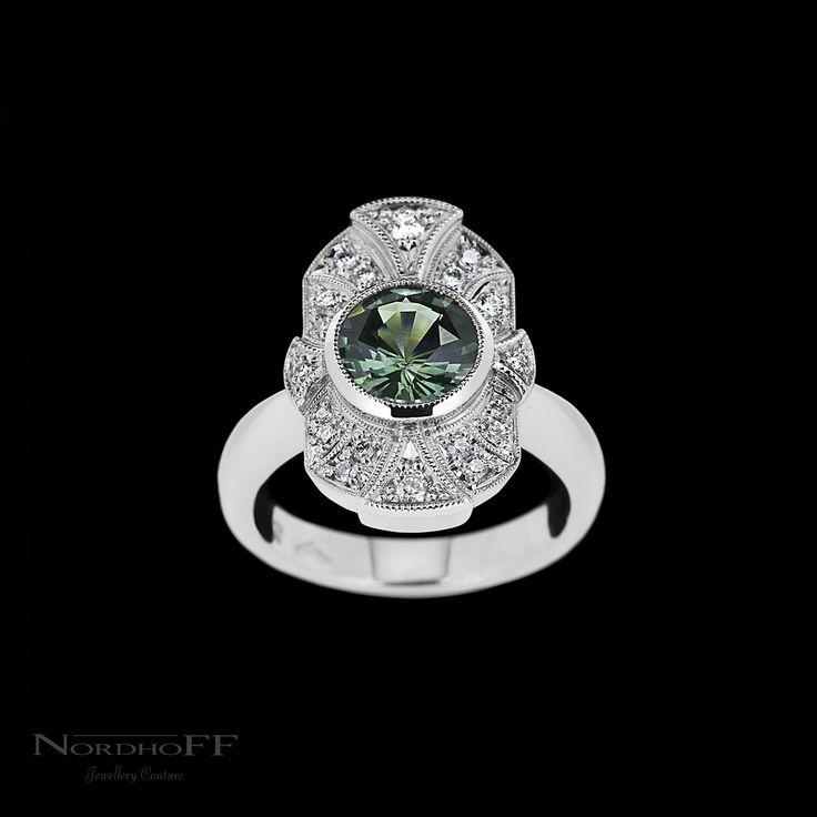When you fall in love with Vintage Art Deco style, but want to start your own story with a blank canvas.... A stunning natural green sapphire sits at the centre of this bespoke platinum engagement ring, the intricate milgrain diamond detail, and the handmade multi level setting complete the Art Deco inspired design.  A bold and unique piece that can be treasured for a lifetime.