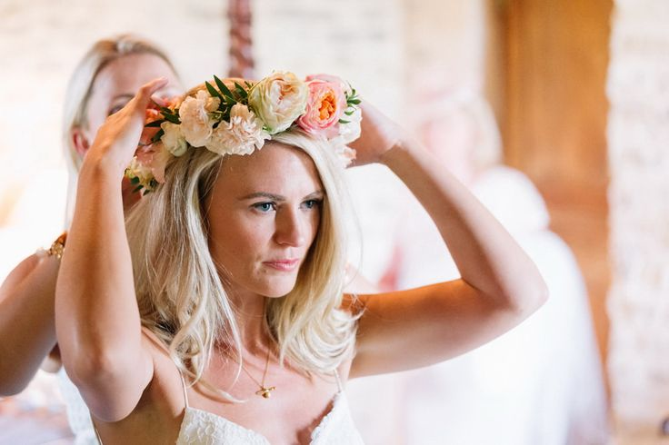 Bridesmaid is helping the bride wear her floral headpiece