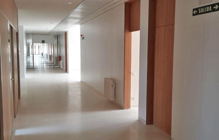 Pasillo del colegio con puertas técnicas de madera color madera
