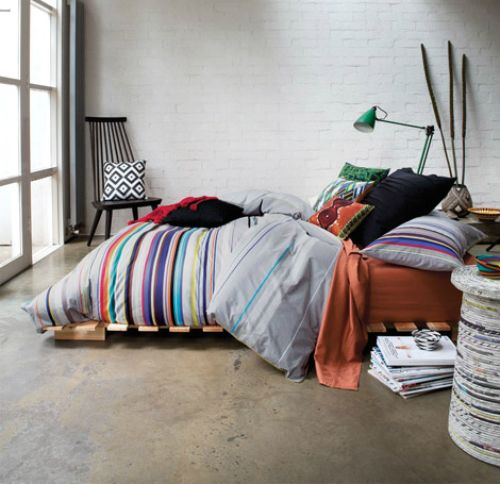 Industrial eclectic bedroom. Polished concrete floor, repurposed crate bed, mixed prints & chic patterns. Cosy.
