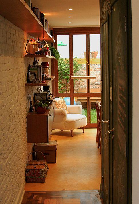 Casa de vila. Cozinha e sala de jantar integradas com vista para o jardim da casa. Parede de tijolo aparente pintado de branco. Piso de cimento queimado amarelo. Porta de vidro com esquadrias de madeira. Prateleiras e aparador de madeira. Lousa verde na porta.