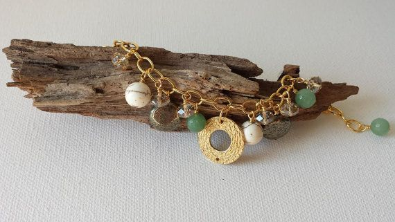 A brass plated pewter disc pendant is at the center of this charming bracelet. A mixture of semi-precious stones have been used to create an earthy yet glamorous piece!