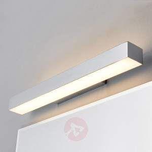 Chromglänzende LED-Badleuchte Kiana- ideal für die Montage über einem Spiegel Diese LED-Badleuchte ist im modernen Stil gehalten - ein Eindruck, der nicht zuletzt deshalb entsteht, weil die Leuchte für die Wandmontage sich in eckiger Form präsentiert und eine glänzende Chromoberfläche hat. Der Lichtschein entweicht auf sanfte Weise, denn die Leuchtmittel werden von satinierten Diffusoren aus Acryl bedeckt. Die längliche Form der Leuchte bewirkt eine Ausleuchtung, die als besonders flächig…