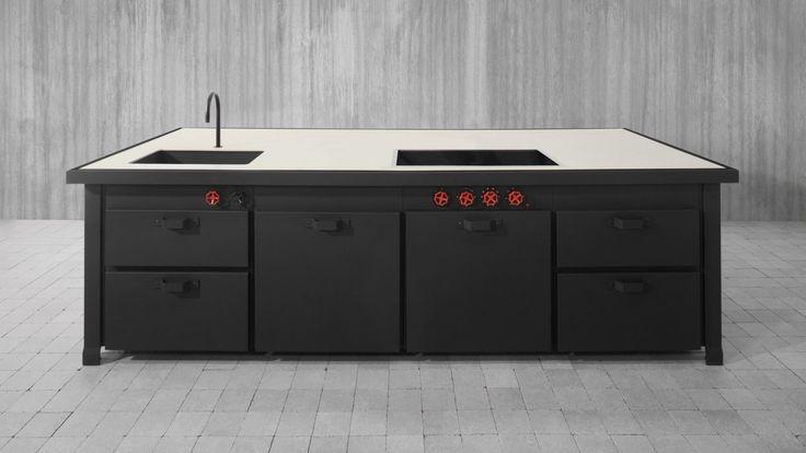 Cucina componibile ad isola, in metallo nero. Piano in cemento. Il piano � attrezzato con lavello, piano cottura ad induzione e %u201Ccoup de feu%u201D.