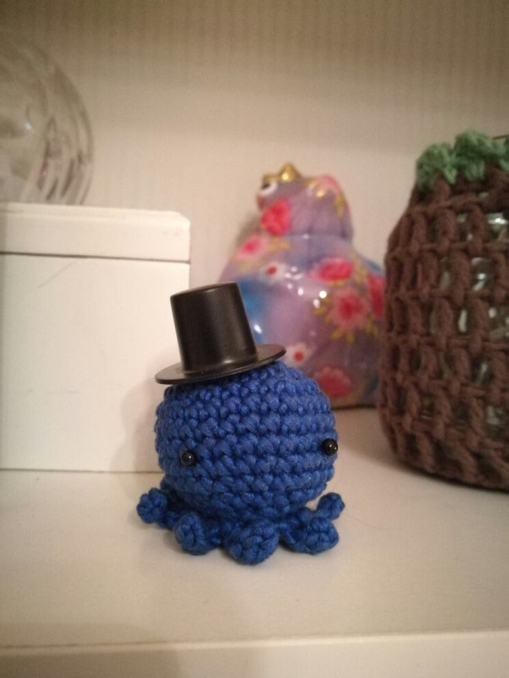 A tiny crotcheted octopus in a tiny top hat (about 3,5 cm)