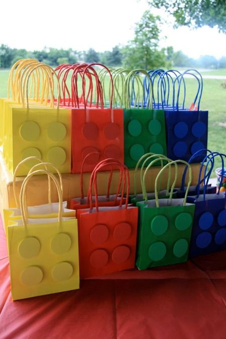 Purchase solid colored handled bags, add matching colored circles and voila – you have Lego goody bags!