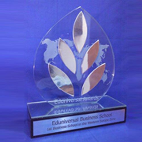 custom glass/metal trophy for Eduniversal Awards. Sandblasted glass with fused metal components mounted on mirror-topped thick black-lacquered wooden base with engraved silver plaque.