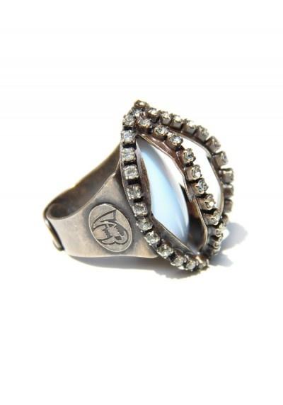 Questo anello è in ottone rodiato color canna di fucile, è interamente realizzato a mano tramite la saldatura di due metà di un fiore utilizzate per formare la gabbia all'interno della quale è imprigionata una pietra cangiante sky. La gabbia è a sua volta decorata con cristalli swarovsky.L'anello è regolabile.Dimensioni:  lunghezza: 3,5 cm