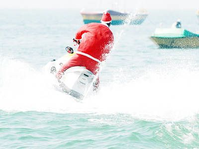 A man dressed in a Santa Claus suit fearlessly zips across the …