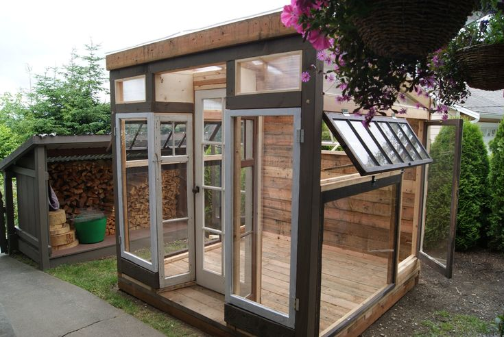 A custom greenhouse with reclaimed windows. It would be so fun to fill this with plants ...