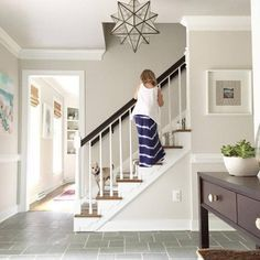 benjamin-moore-edgecomb-gray-by-young-house-love-showin-in-entryway-or-foyer-with-white-stairs-and-tile-flooring