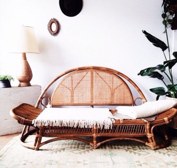 Beautiful old bohemian day bed in rattan. Cane back and elevated sides make for a beautiful piece. This comes with a firm and comfortable cushion