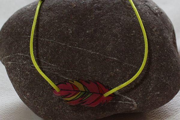 Bracelet réalisé en cordon ciré jaune avec connecteur plume en plastique fou
