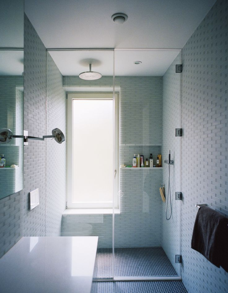Triple-glazed, frosted windows emit soft, filtered light against pale gray and blue surfaces inthe master bathroom. Lucian Field matte-glass and Lucian Mosaics penny round tiles, both by Ann Sacks, line the floor and walls.