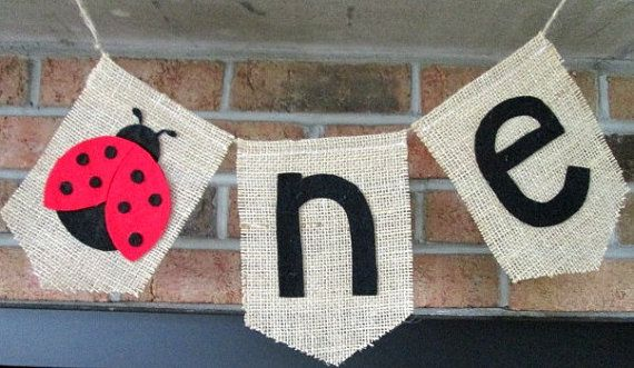 Ladybug ONE burlap Banner  Handmade by me, in my smoke-free home.  This cute ladybug banner would make a cute backdrop for babies cake smash and then could be hung from highchair or cake table. Ladybug is made from red and black felt, all hand cut by me. The n and e are also made from black felt.  The individual burlap flags measure approximately 5-inches wide by 7-inches tall. Total length(including extra jute for hanging) is 44-inches. The flags make up 18-inches of the banner.  Thank you…