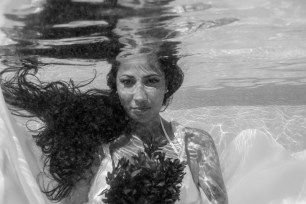 Underwater bride portrait with flowers in the swimming pool at the Westin hotel resort in Fiji by Anais Photography for trash the dress