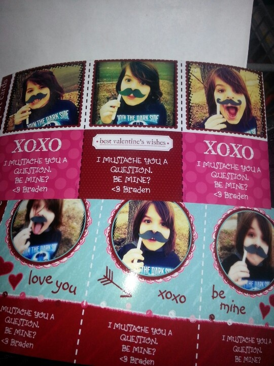 Homemade Valentine's cards: make mustaches using card stock and popsicle sticks. Take a few different photos with your model (in this case, my model is my 7 yr old, Braden) wearing different mustaches. Go to walmart.com and find a vday card template you like (I chose the 3 in one cut away card) and edit online. Buy 3 5/8 x 6 1/2 in envelopes. Make additional mustaches to include with each Valentine's card!