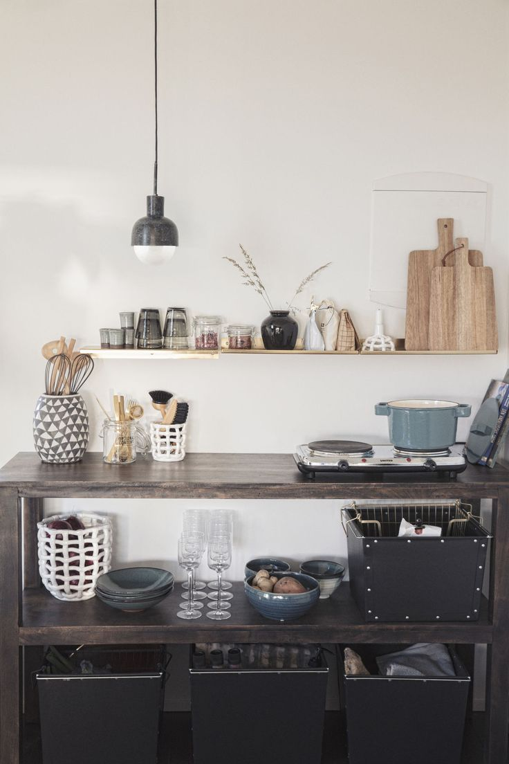 In the tiny kitchen area, open shelves serve double duty as both storage space and decorative statements. Here, a personal selection of kitchen necessities serves as an effective instrument to create a stylish and welcoming ambience.