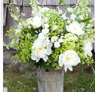 in-season white and green flowers in tall galvanized tin buckets.