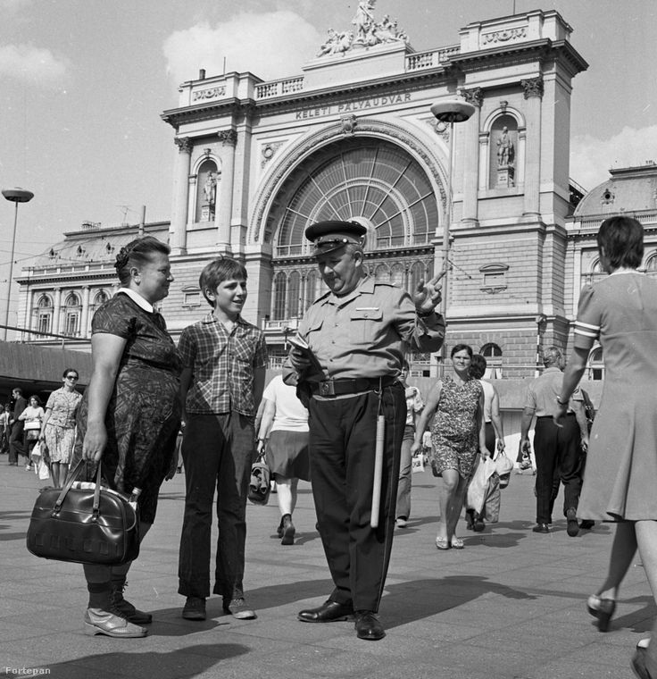 Kristóf László 1976 májusában a Keleti pályaudvarnál fotózta a rendőrségi munkát. A segítőkész rendőr vidéki állampolgárokat igazít el a nagyvárosi dzsungelben.