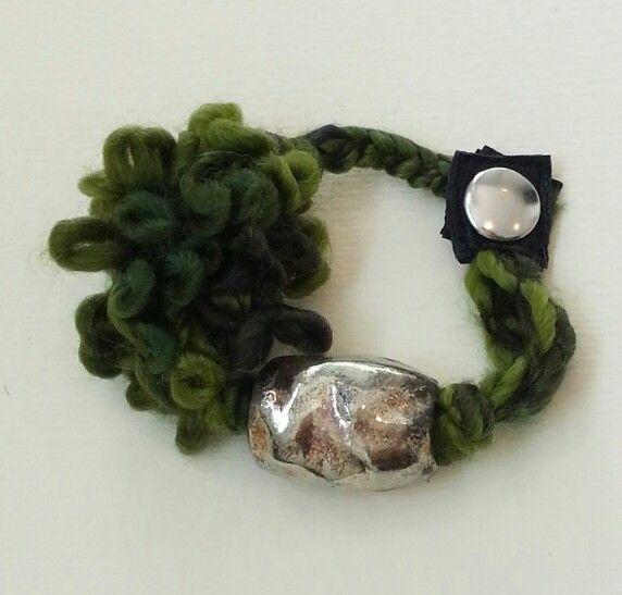 Green and gold handmade bracelet made with wool, leather, raku ceramic bead