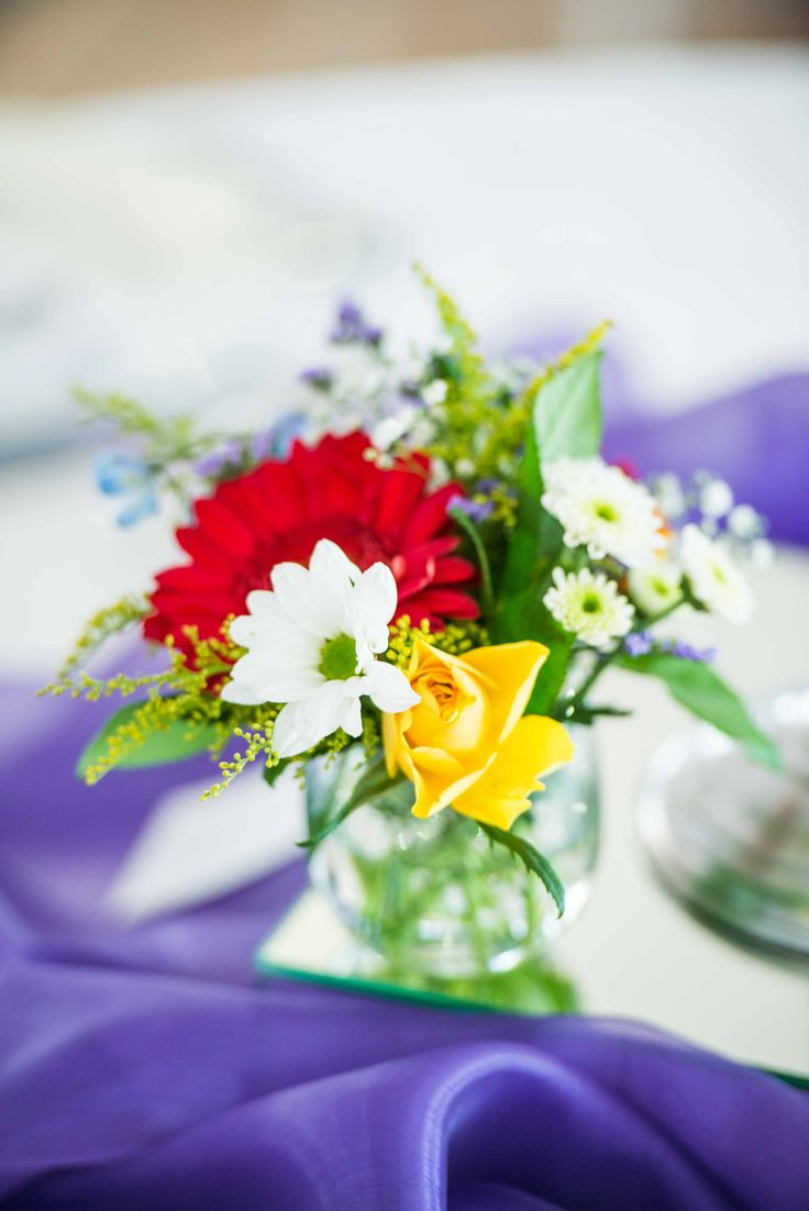 Monte Vista Venue rainbow centerpiece with a white candles on a silver candelabra and a small glass bowl with a mix of flowers in, all on a mirror box surrounded by purple organza.