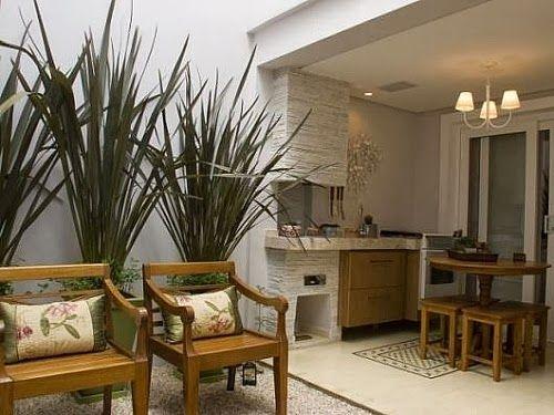 Churrasqueira com revestimento em pedra filetada (clara), piso com tapete de ladrilhos e área externa com chão coberto de pedriscos brancos.