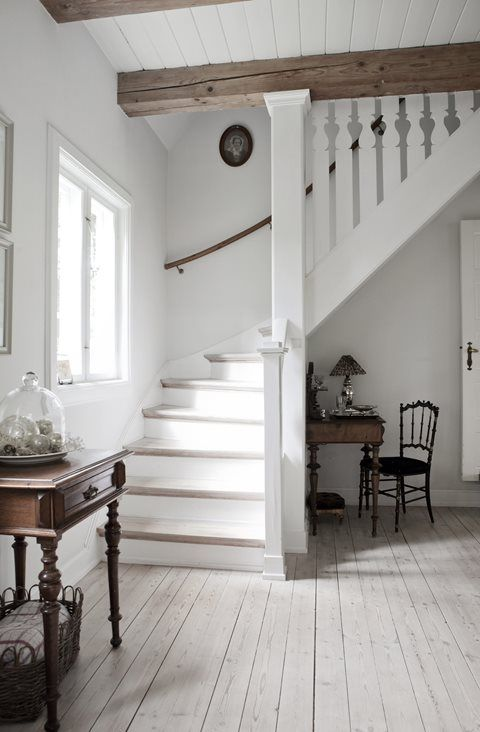 white ceiling with wood beams; guard railings on stairs